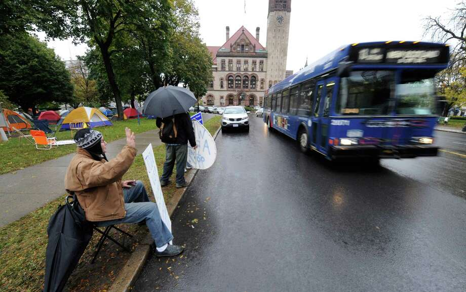 Ray Drake waves to the passersby at the Occupy Albany tent city in Academy Park in Albany, N.Y. October 26, 2011. (Skip Dickstein/Times Union archive) Photo: Skip Dickstein / 2011