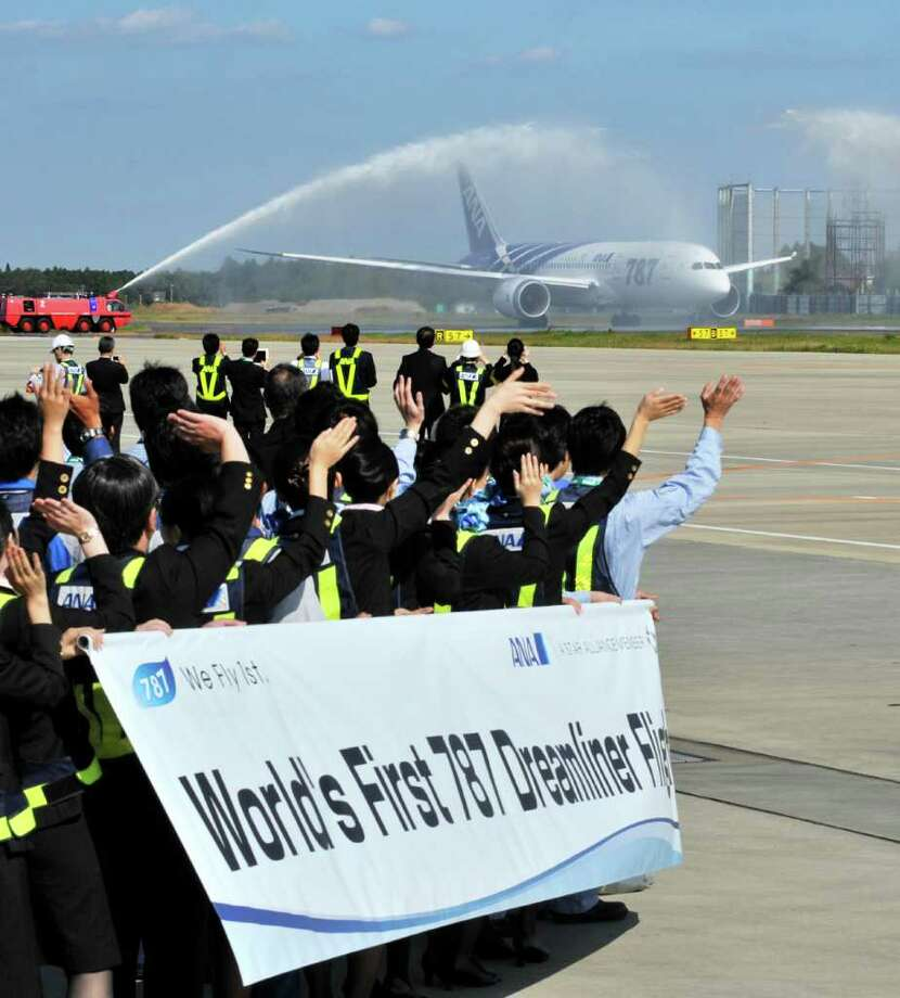 All Nippon Airways (ANA) ground crew wave goodbye to the company's first commercial flight of a Boeing 787 Dreamliner on its departure for Hong Kong on October 26, 2011 at Narita Airport in Chiba prefecture, suburban Tokyo.  Boeing's new 787 Dreamliner was to make its first commercial flight, giving a handful of deep-pocketed passengers the chance to fly into history on what is touted as an aviation breakthrough.     AFP PHOTO / KAZUHIRO NOGI Photo: KAZUHIRO NOGI, AFP/Getty Images / 2011 AFP