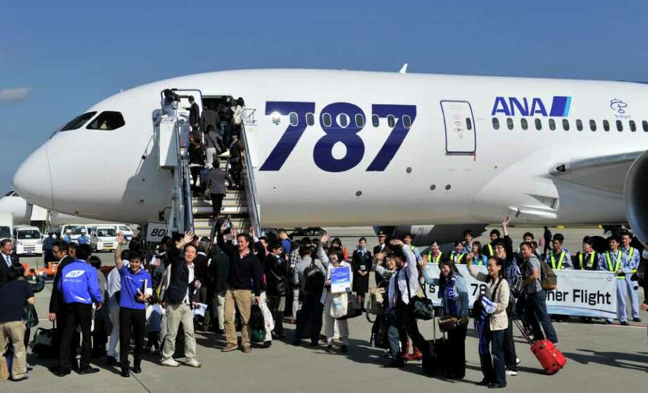 Passengers board onto Boeing new 787 Dreamliner jet on its first commercial flight operated by All Nippon Airways (ANA) at Narita Airport, Chiba prefecture, suburban Tokyo prior to its departure for Hong Kong on October 26, 2011. Boeing's new 787 Dreamliner was to make its first commercial flight, giving a handful of deep-pocketed passengers the chance to fly into history on what is touted as an aviation breakthrough. AFP PHOTO / KAZUHIRO NOGI Photo: KAZUHIRO NOGI, AFP/Getty Images / 2011 AFP
