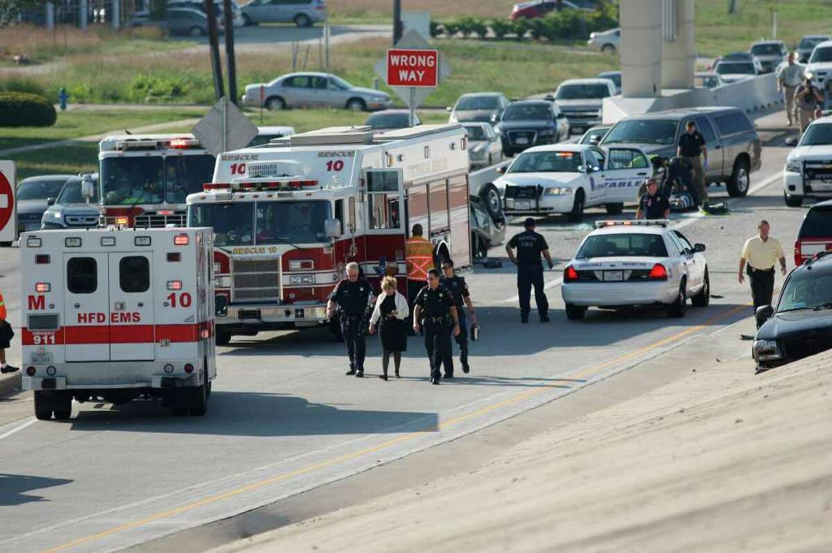 HPD officers escort a woman to an ambulance at the scene of a multi-car accident on the northbound Bellaire exit ramp from Beltway 8 on Wednesday, Oct. 26, 2011, in Houston. ( Andrew Richardson / Houston Chronicle )