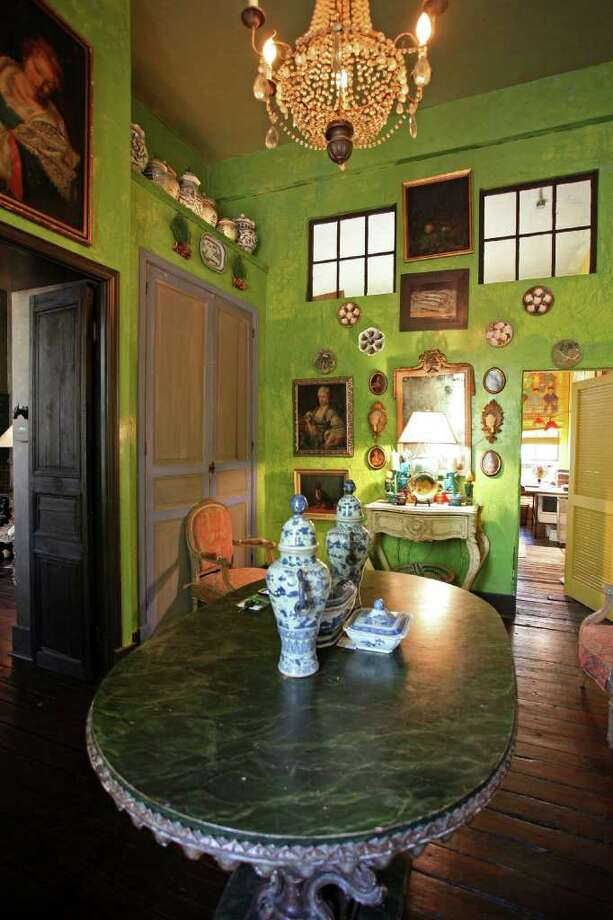 Griffith had her son paint the entry sour apple green. She found the green doors trimmed in purple in Los Angeles and had them shipped home and built around them. Art, dishes and pottery are displayed in the entry. Photo: DANNY WARNER