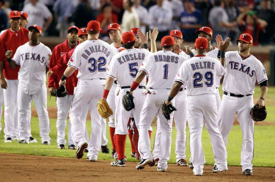 The Texas Rangers react after winning Game 5 of baseball's World Series 4-2 over the St. Louis Cardinals, Monday, Oct. 24, 2011, in Arlington, Texas. The Rangers took a 3-2 lead in the series. Rain postponed Wednesday's game. (AP Photo/Eric Gay) Photo: Eric Gay