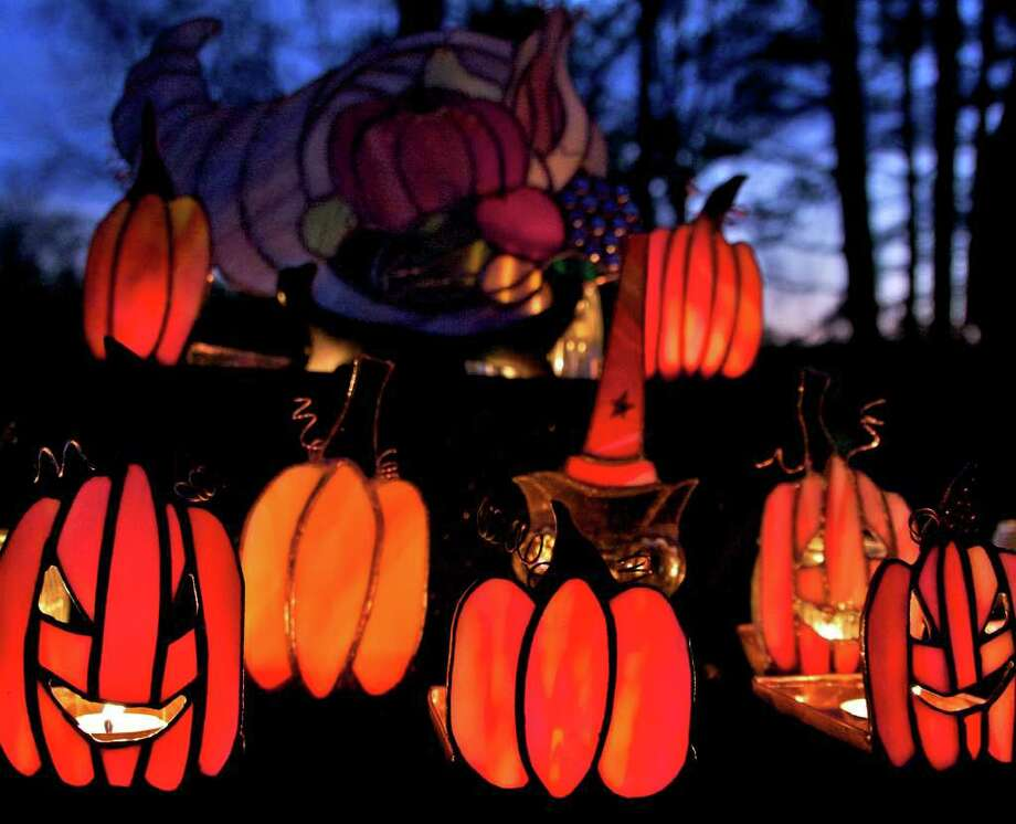 "'Pumpkins in the Park'  SPECTRUM/Beautiful  pumpkins light up the night Saturday at Harrybrooke Park in New Milford. The pumpkins are actually stained-glass images from Billie Jo's booth, specializing in custom designs from Prospect. The event was the Friends of Harrybooke Park's second annual fundraiser called ""Pumpkins in the Park."" For the story and more photos, see Page S23 or check www.newmilfordpsectrum.com. Photo: Trish Haldin"