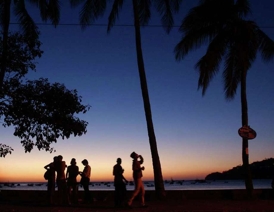 SOME SUNSET: A group of tourists gather on the beach of San Juan del Sur,  Nicaragua. (AP Photo/Esteban Felix) Photo: ESTEBAN FELIX / AP