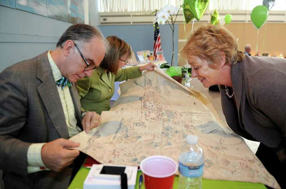 Appraisers Lark Mason and Helen Kippax, formerly of Sotheby's, look at an early 20th centrury silk map of the German colony of Tsingtao in China at the third annual Fall Boutique and Appraisal Day hosted by Time for Lyme's third annual fundraising boutique at Christ Church Parish Hall in Greenwich.  Getting the map appraised is its owner, Brigitte Recchione.  Proceeds from the appraisal were donated to Time for Lyme. Photo: Helen Neafsey / Greenwich Time