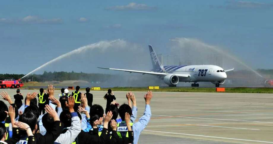 All Nippon Airways  ground crew members wave goodbye to the company's first commercial flight of a Boeing 787 Dreamliner on its departure for Hong Kong on October 26, 2011 at Narita Airport in Chiba prefecture, suburban Tokyo.  Boeing's new 787 Dreamliner was to make its first commercial flight, giving a handful of deep-pocketed passengers the chance to fly into history on what is touted as an aviation breakthrough. Photo: KAZUHIRO NOGI, Getty / AFP