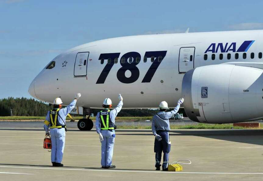 All Nippon Airways  ground crew members wave goodbye to the company's first commercial flight of a B