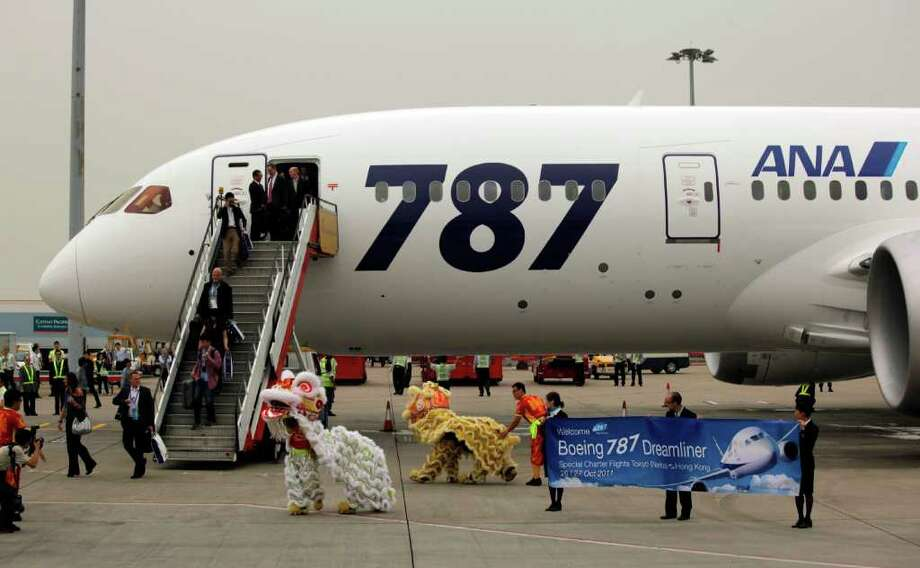 Passengers of an All Nippon Airways Boeing 787 are welcomed by lion dance to celebrate the airplane's inaugural commercial flight from Japan, at Hong Kong International Airport on Wednesday, Oct. 26, 2011. The jet, nicknamed The Dreamliner by Boeing Corp., was flown by Japan's All Nippon Airways and was packed with aviation reporters and enthusiasts. Photo: Vincent Yu, Associated Press / AP