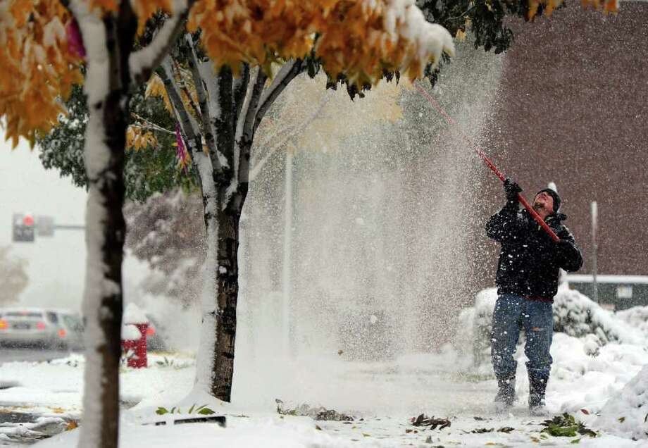 Gabe Jones knocks snow from the trees at Englewood Civic Center in Englewood, Colo.,  Wednesday, Oct. 26, 2011. For the Wednesday forecast snow is likely through late afternoon with accumulation of 2 to 5 inches. Highs near 30. Photo: Craig F. Walker, Associated Press / The Denver Post