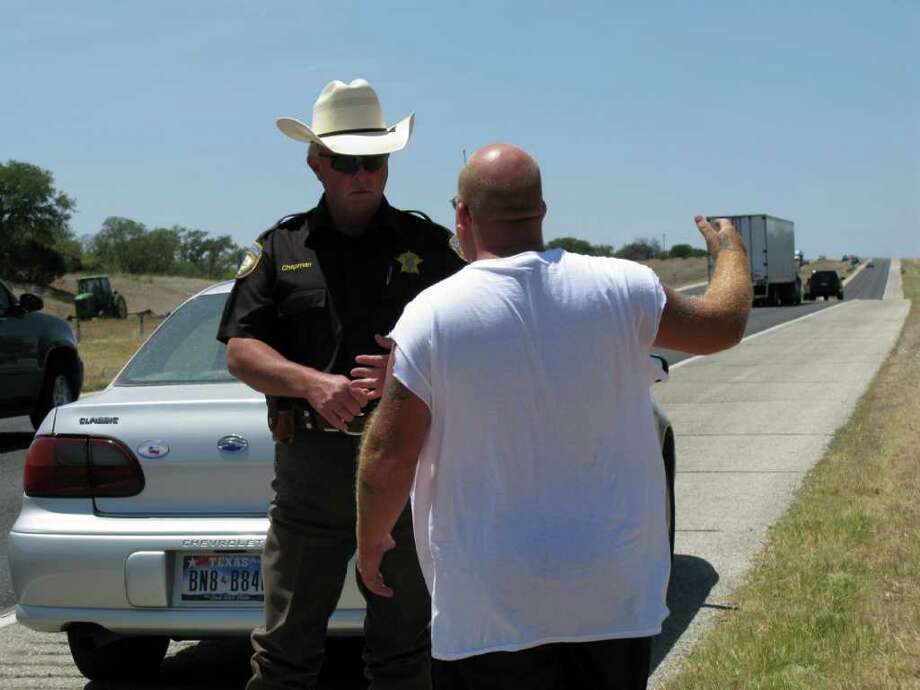 Mike Chapman, investigator for the 198th Judicial District police, interviews a motorist beside Interstate 10 in Kerr County. Photo: Zeke MacCormack, Zeke@express-news.net / SAN ANTONIO EXPRESS-NEWS