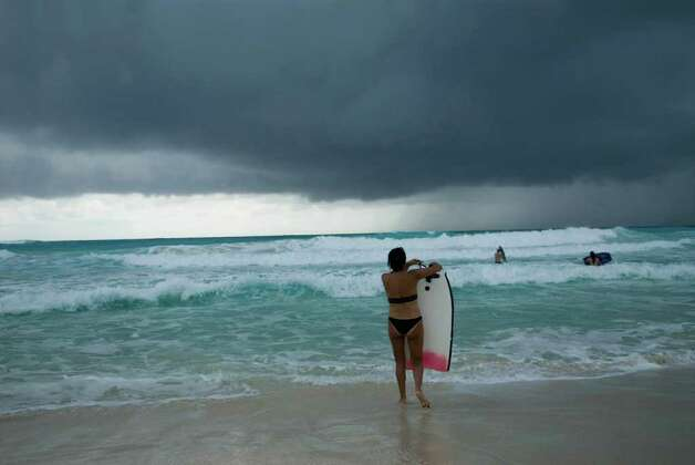 A tourist carries her surfing board while a storm approaches in Cancun, Quintana Roo state, Mexico on October 26, 2011. Hurricane Rina churned toward Cancun and other international tourist resorts Wednesday, with Mexico's Caribbean coast beginning evacuations as it braced for a direct hit. Photo: JOSE DOMINGUEZ, Getty / AFP
