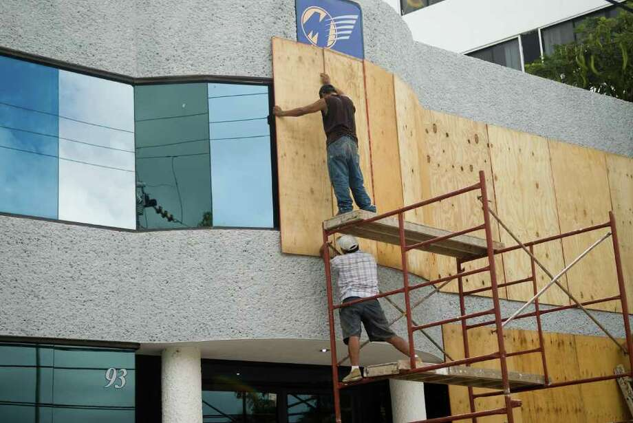 Workers cover the windows of a building in preparation for the arrival of Huricane Rin, in Cancun, Quintana Roo state, Mexico on October 26, 2011. Photo: JOSE DOMINGUEZ, Getty / AFP