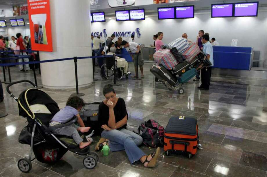 People wait at the international airport ahead of the passage of Hurricane Rina in Cancun, Mexico, Wednesday Oct. 26, 2011. Tourists fleeing Hurricane Rina crowded Cancun's airport Wednesday even as the cyclone lost some of its punch while heading toward Mexico's resort-studded Caribbean coast. Photo: Marco Ugarte, Associated Press / AP