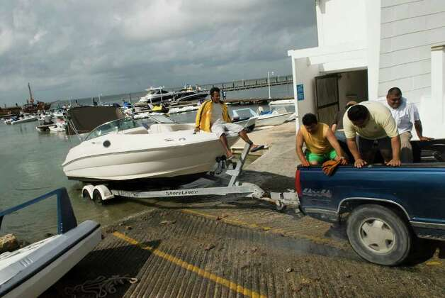 People take out their boats from the beach in Cancun, Quintana Roo state, Mexico on October 26, 2011. Photo: JOSE DOMINGUEZ, Getty / AFP