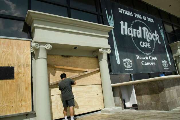 A worker covers the windows and door of a coffee shop in preparation for the arrival of hurricane Rina in Cancun, Quintana Roo state, Mexico on October 26, 2011.  Hurricane Rina weakened Wednesday but held its course for a direct hit on Mexico's tourist beaches, where evacuation orders were issued for vulnerable coastal areas. Photo: JOSE DOMINGUEZ, Getty / AFP
