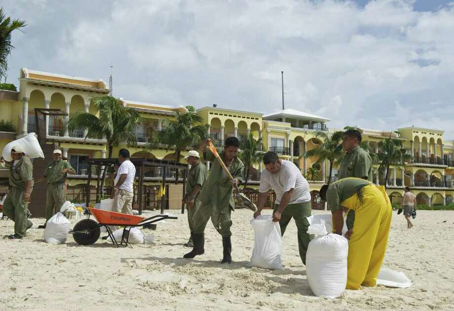 Hotel workers fill bags with sand in preparation for the arrival of Huricane Rin, in Playa del Carmen, Quintana Roo state, Mexico on October 26, 2011. Photo: RONALDO SCHEMIDT, Getty / AFP