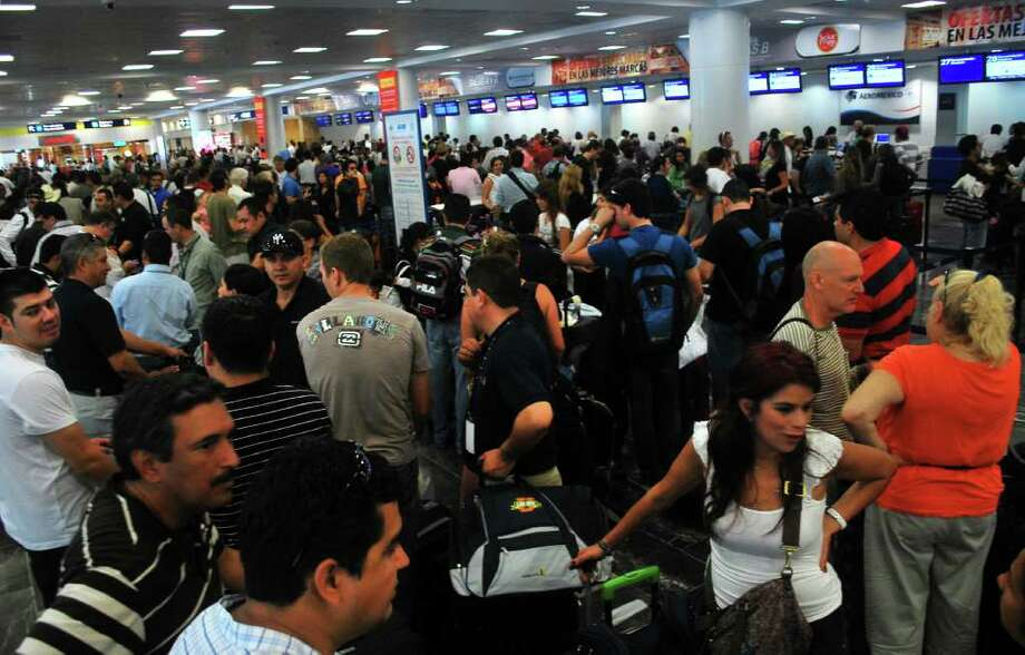 People stand in line to check-in at the international airport ahead of the arrival of Hurricane Rina in Cancun, Mexico, Wednesday Oct. 26, 2011. Photo: Israel Leal, Associated Press / AP