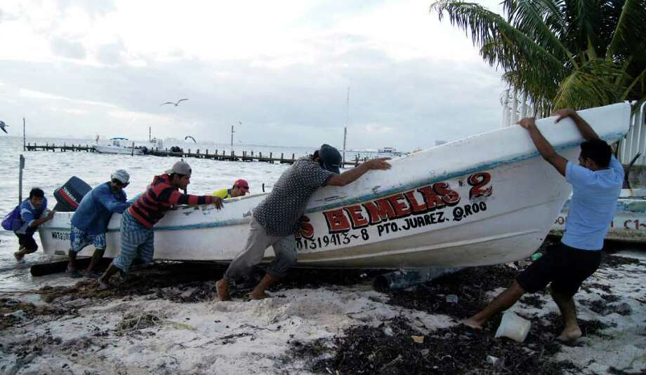 Fishermen secure their boat in anticipation of Hurricane Rina's arrival in Cancun, Mexico, Tuesday Oct. 25, 2011. Photo: Israel Leal, Associated Press / AP