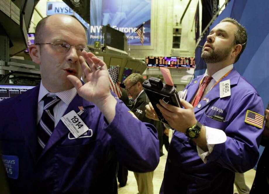 Specialist Dermot Bermingham, left, and trader Kevin Lodewick, work on the floor of the New York Stock Exchange Wednesday, Oct. 26, 2011. (AP Photo/Richard Drew) Photo: Richard Drew