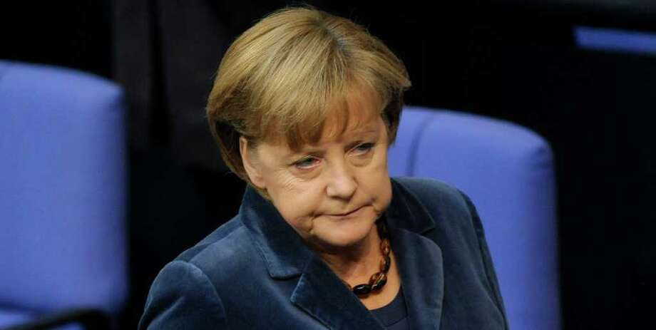 German Chancellor Angela Merkel  reacts  during a debate at  the German federal parliament, Bundestag,  in Berlin, Germany, Wednesday, Oct. 26, 2011. Merkel  is calling for the private sector to make a significantly larger contribution than previously agreed to reduce Greece's debt burden.  Merkel  said the aim of a European summit Wednesday must be a solution that allows for Greece to cut its debt load to 120 percent of gross domestic product by 2020. (AP Photo/dapd/Michael Gottschalk) Photo: Michael Gottschalk / dapd