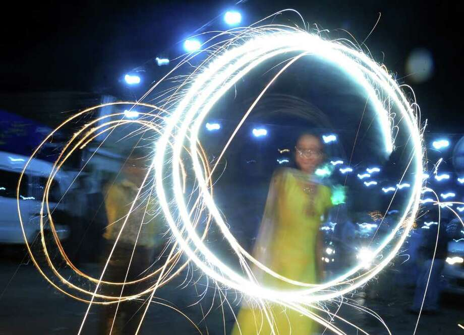 Pakistani Hindu children wave sparklers on the occasion of Diwali. Photo: RIZWAN TABASSUM, Getty / AFP
