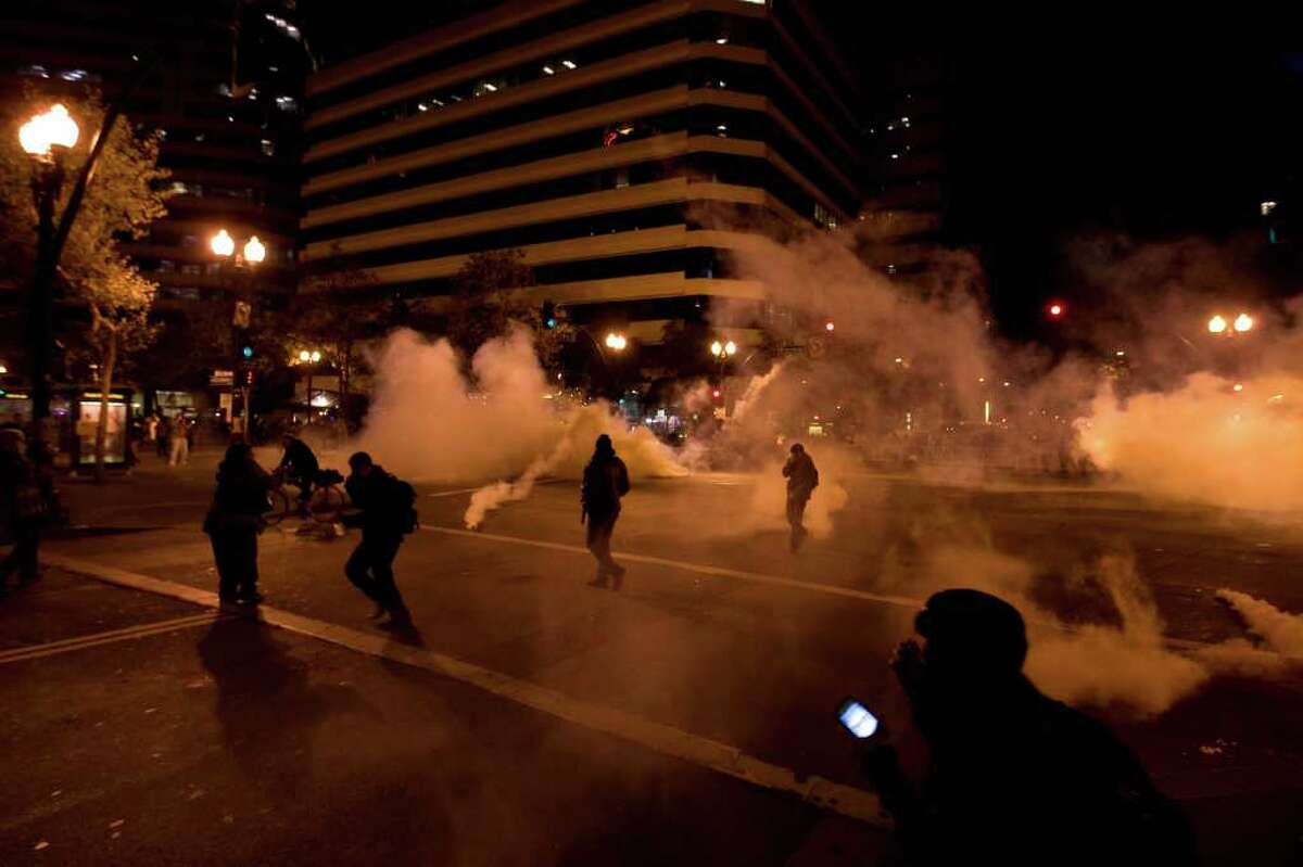 Occupy Wall Street protesters run from tear gas deployed by police at 14th Street and Broadway in Oakland, Calif., Tuesday, Oct. 25, 2011.