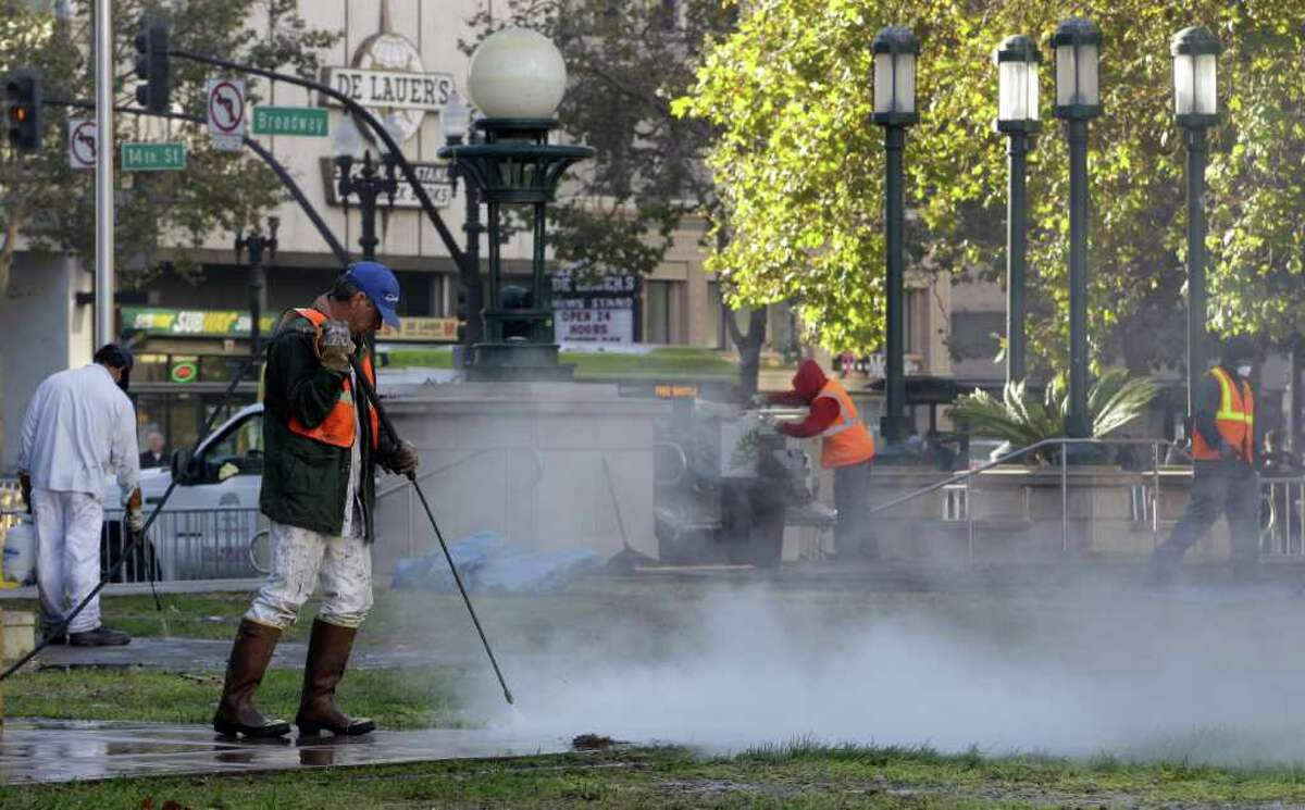 Oakland public works personnel use steam cleaners as they continue to sanitize Frank H. Ogawa plaza Wednesday, Oct. 26, 2011, in Oakland, Calif. Occupy Oakland protestors have been trying to stay in Frank H. Ogawa plaza since being evicted early Tuesday morning.