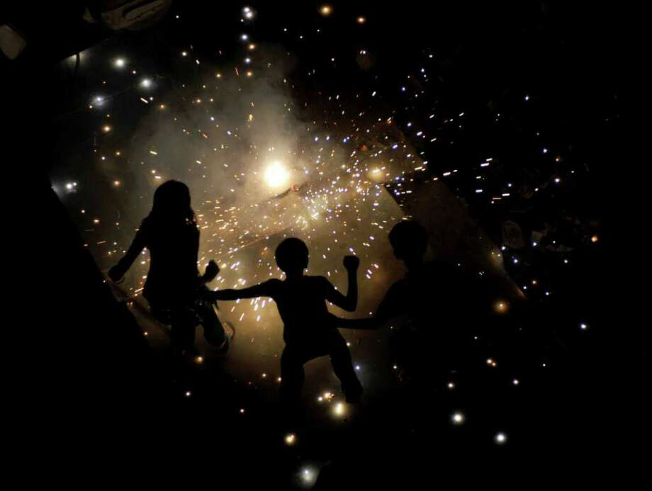 Indian children light fireworks in New Delhi, on October 26, 2011, for Diwali, the Hindu festival of lights. The festival marks the victory of good over evil and commemorates the time when Hindu God Lord Rama achieved victory over Ravana and returned to his kingdom Ayodhya after 14 years in exile. Photo: SAJJAD HUSSAIN, Getty / AFP