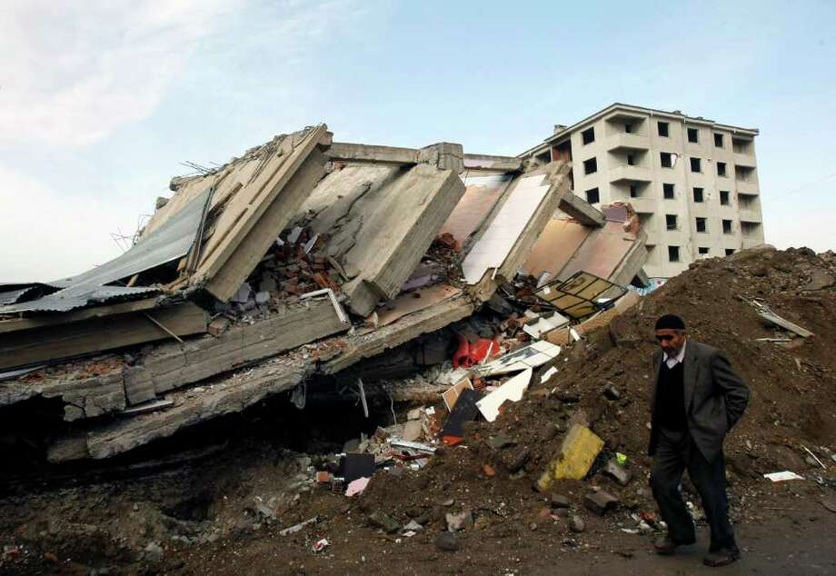A man walks by a destroyed building in Ercis, eastern Turkey, Wednesday, Oct. 26, 2011. Excavators with heavy equipment began clearing debris from some collapsed buildings in Ercis after searchers removed bodies and determined there were no other survivors. The 7.2-magnitude quake Sunday has killed at least 461 people and injured over 1,350. Photo: Burhan Ozbilici, AP / AP