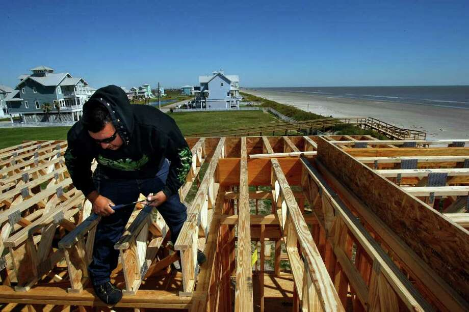JOHNNY HANSON : CHRONICLE OPEN TO GULF: Juan Pena works Wednesday on a new home in the Beachside Village neighborhood on Galveston's West End, about a mile from the city's seawall. Scientists at Rice University question whether anyone should live on that end of the island, a topic of growing debate. Photo: Johnny Hanson / © 2011 Houston Chronicle