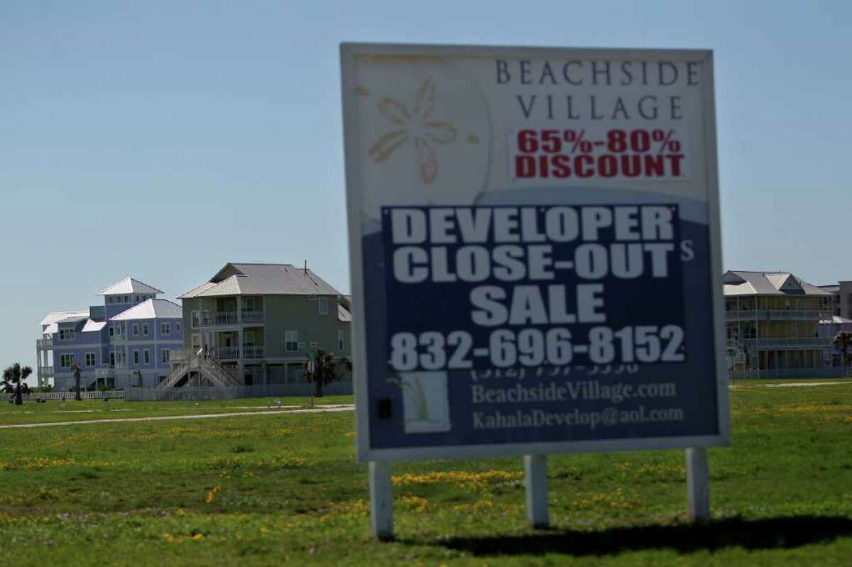 A sign advertises a close-out sale for the newly built homes in the Beachside Village neighborhood on Galveston's West End about a mile from the city's protective seawall Wednesday, Oct. 19, 2011. A new book published by Rice University about Galveston Island questions whether anyone should live on its western end, a subject of increasing debate on the island. The book recommends that all of the human habitation be pulled back behind the sea wall. ( Johnny Hanson / Houston Chronicle )