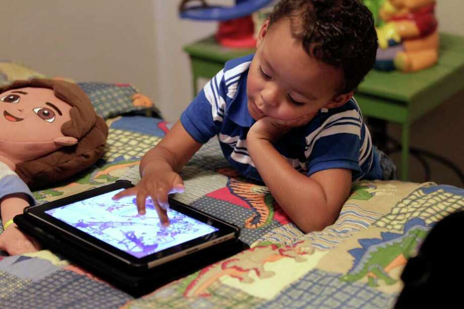 In this Friday, Oct. 21, 2011 photo, Frankie Thevenot, 3, plays with an iPad in his bedroom at his home in Metairie, La. About 40 percent of 2- to 4-year-olds (and 10 percent of kids younger than that) have used a smartphone, tablet or video iPod, according to a new study by the nonprofit group Common Sense Media.   (AP Photo/Gerald Herbert) Photo: Gerald Herbert