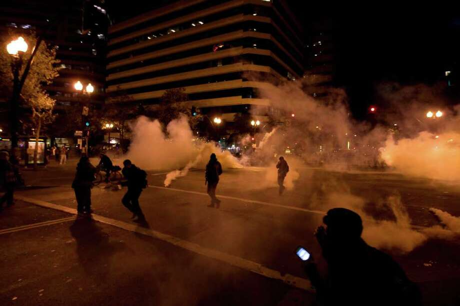 Occupy Wall Street protesters run from tear gas deployed by police at 14th Street and Broadway in Oakland, Calif., Tuesday, Oct. 25, 2011. (AP Photo/Darryl Bush) Photo: Darryl Bush