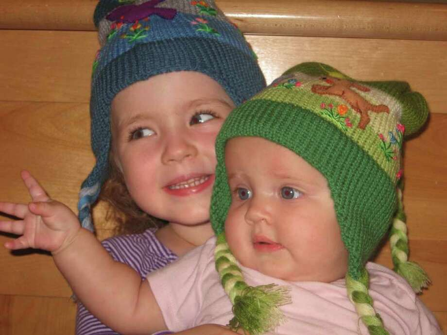 Kate and Mae Barnard model hand knitted hats from the Darien Nature Centerís Holiday Fair Trade Market. Photo: Contributed Photo
