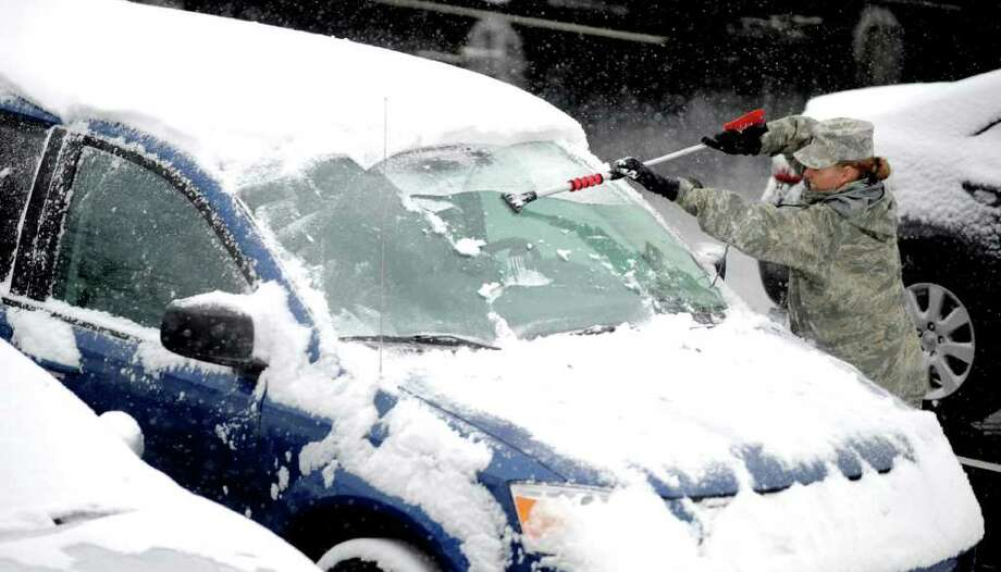 The cold front is not expected to bring snow to San Antonio, but a system did drop a bunch of the white stuff in Colorado. Master Sgt. Amy Wilson scrapes her windshield in the parking lot outside of Harmon Hall at the Air Force Academy north of Colorado Springs, Colo., Wednesday morning, Oct. 26, 2011. There was about 4 inches of wet snow on grassy areas at the Academy by mid-morning. Photo: AP
