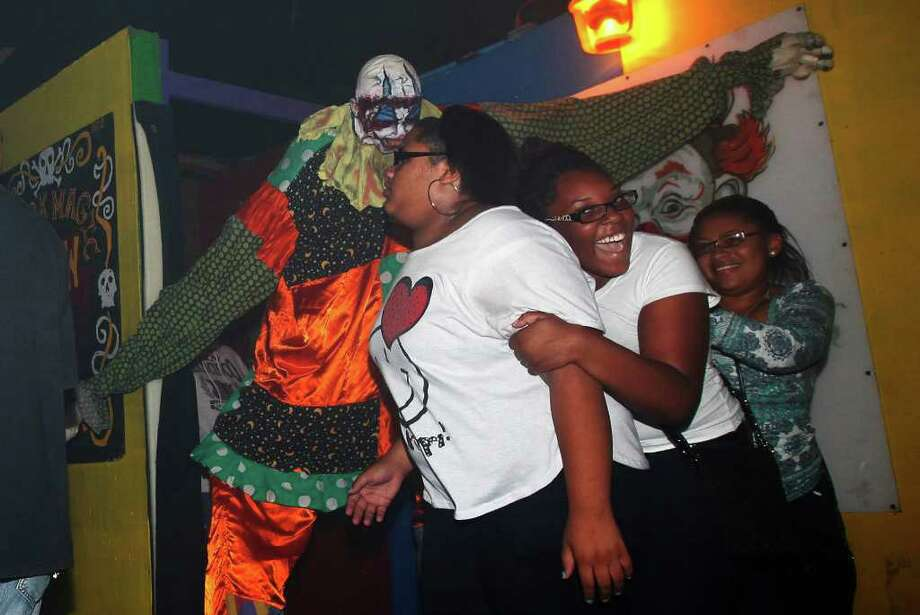 Visitors to Nightmare on Grayson Street get a fright from actor Jerome Barideaux (left) dressed as a seven-foot clown during the haunted house's opening night on Wednesday, Oct. 26, 2011. Photo: Kin Man Hui, / / San Antonio Express-News