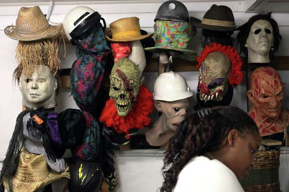Masks from previous years line a wall in the costume area of Nightmare on Grayson Street on Wednesday, Oct. 26, 2011. Most of the masks have been retired for more customized masks with more detail according to the haunted house actors. Kin Man Hui/kmhui@express-news.net Photo: Kin Man Hui, / / San Antonio Express-News