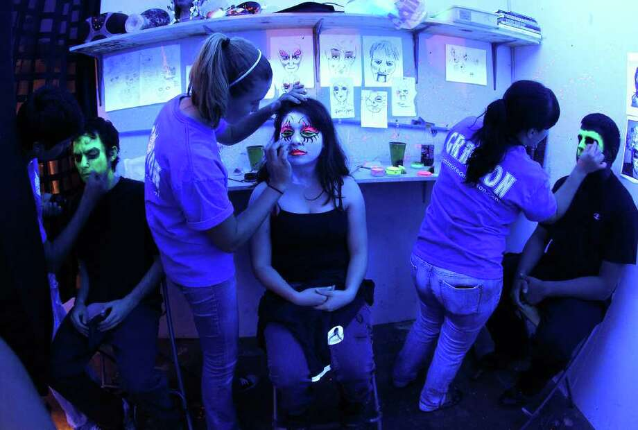 Actress Beija Colon (center) gets makeup work by artist Tara Burns (left of Colon) moments before Nightmare on Grayson Street's opening night of their haunted house on Wednesday, Oct. 26, 2011. About 30 actors are used to scare visitors at the haunted house. Kin Man Hui/kmhui@express-news.net Photo: Kin Man Hui, / / San Antonio Express-News