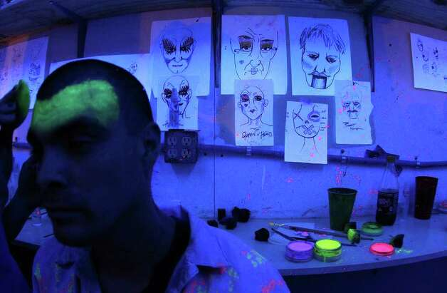 Actor David Hernandez (left) receives makeup in a black-light room to filled with sketches moments before Nightmare on Grayson Street's opening night on Wednesday, Oct. 26, 2011. Kin Man Hui/kmhui@express-news.net Photo: Kin Man Hui, / / San Antonio Express-News