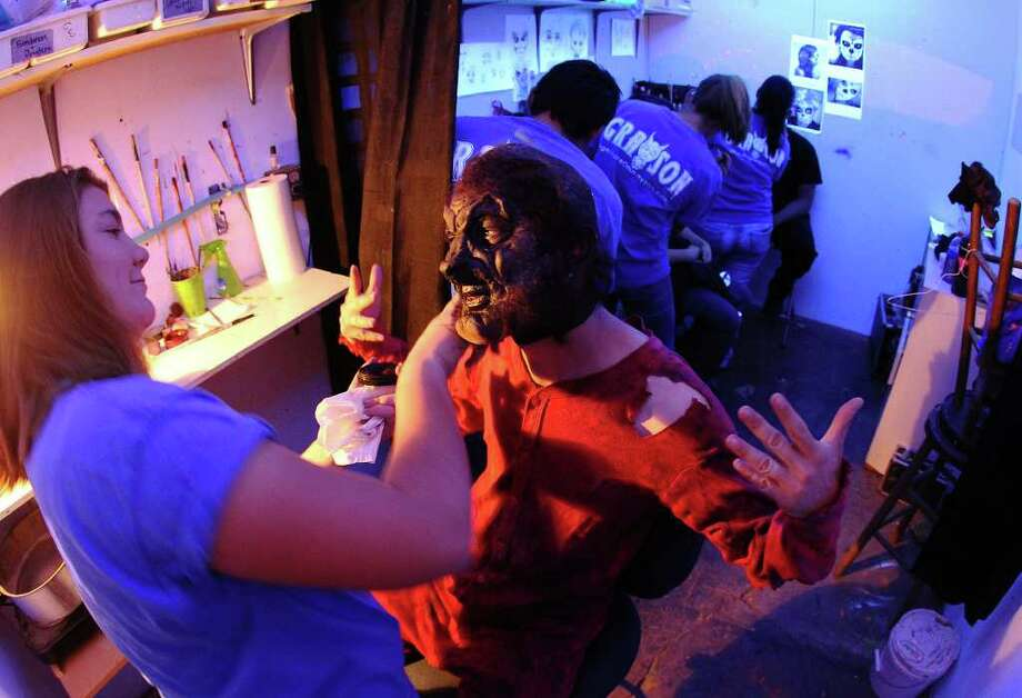 Actor Jackson Cusack (center) receives finishing touches on his werewolf mask by makeup artist Shauna Burns (left) moments before Nightmare on Grayson Street's opening night on Wednesday, Oct. 26, 2011. Kin Man Hui/kmhui@express-news.net Photo: Kin Man Hui, / / San Antonio Express-News