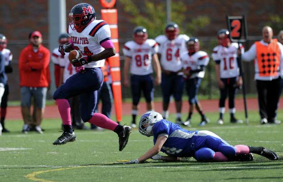 Brien McMahon's Chris Jerome escapes a tackle from Fairfield Ludlowe's Matthew White Saturday, Oct. 22, 2011 during their football game at Taft Field in Fairfield, Conn. Photo: Autumn Driscoll / Connecticut Post
