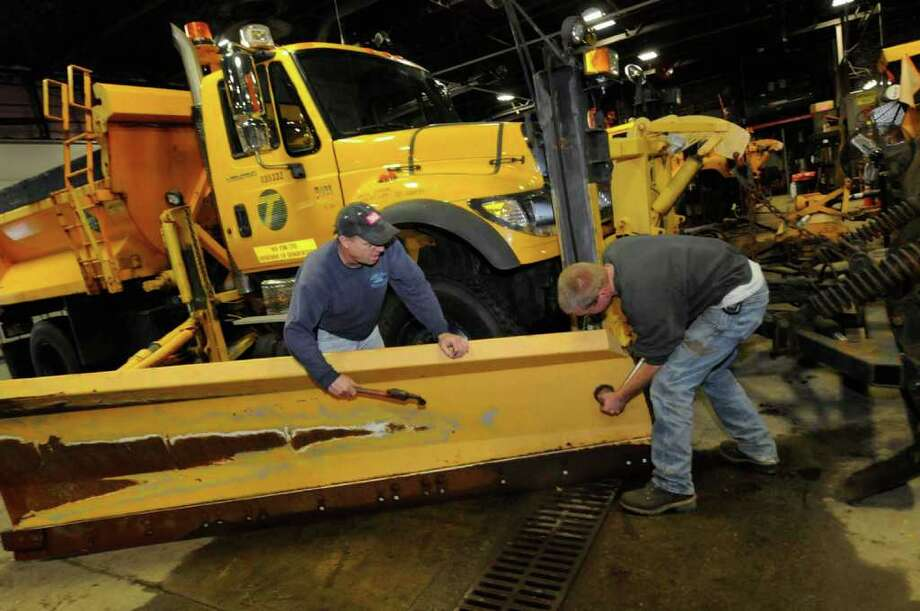 Highway maintenance workers Tim Cocran,left, and Kevin Stewart ready a snow plow for possible weather conditions at the DOT garage in Latham, NY Thursday, Oct. 27, 2011.( Michael P. Farrell/Times Union) Photo: Michael P. Farrell