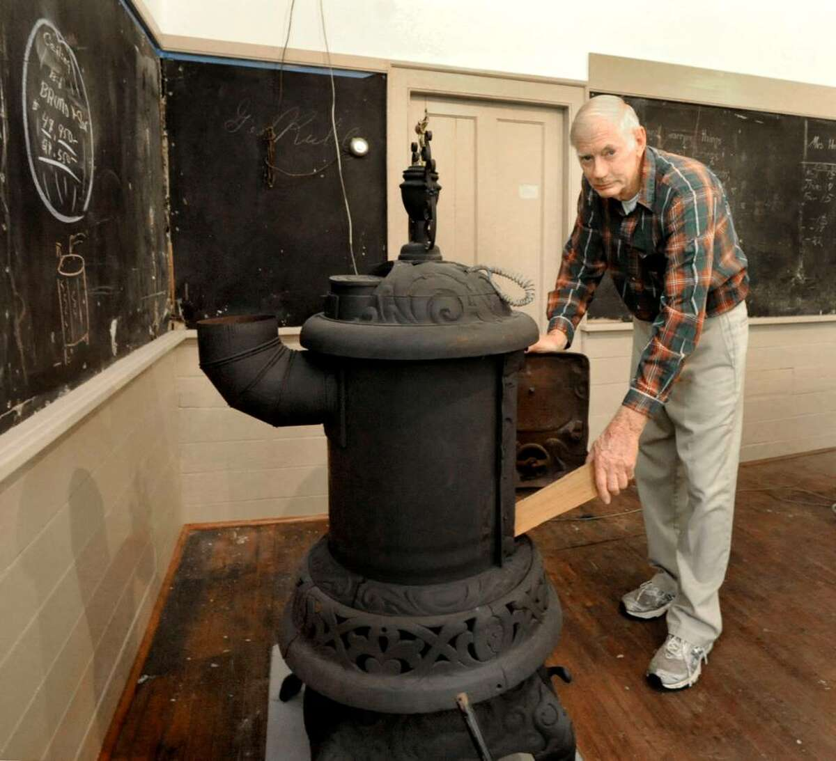 Ed Rockwell, a member of the Plumtrees Landmark Preservation committe,who attended the school from 1941 to 45, loads wood into a vintage woodstove to create a sense of realism inside the Bethel school on monday.
