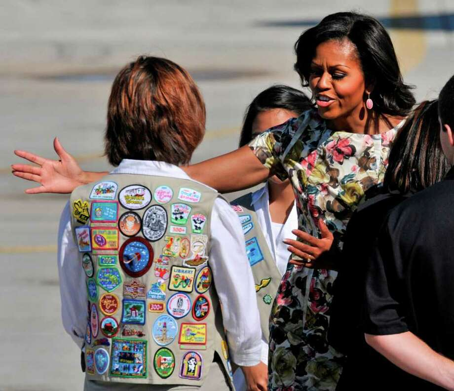 First Lady Michelle Obama reaches out to hug Helene Fischer, 16, a member of the Girl Scout Board of Directors for north Florida,  after Obama's plane landed at Jacksonville Naval Air Station Thursday, Oct.  27, 2011 in Jacksonville, Fla. Photo: Will Dickey, Associated Press / Will Dickey/Florida Times-Union