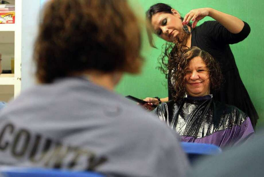 Bexar County Jail female inmate Marie Jackson beams while stylist Denise Duque works on Jackson's hair on Thursday, Oct. 27, 2011. Jackson, with about 45 other inmates, donated a lock of her hair to the Locks of Love program that helps provide hairpieces to children who suffer hair loss due to illness . The inmates had their long sections of hair removed and then had a stylist finish the cut with a shorter, newer coiffure. This occasion marked the first time inmates from Bexar County Jail donated their hair to the cause. Photo: Kin Man Hui, / / San Antonio Express-News