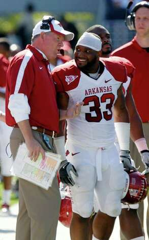 Arkansas football coach Bobby Petrino and running back Dennis Johnson (33) confer during an NCAA college football game against Mississippi Saturday, Oct. 22, 2011, in Oxford, Miss. Arkansas won 29-24. Photo: Rogelio V. Solis