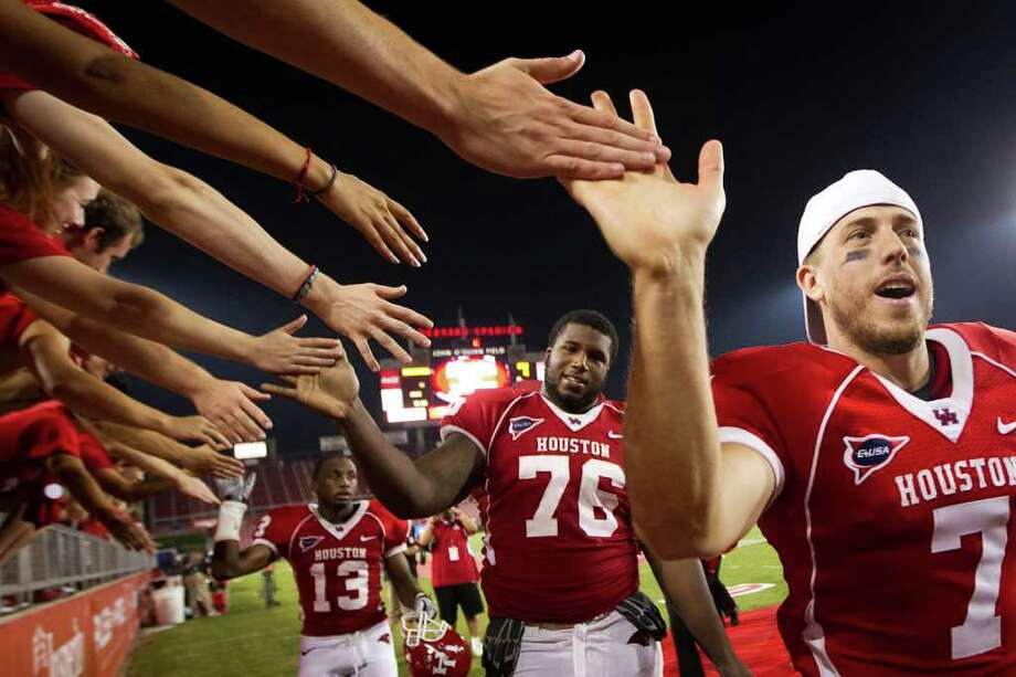 Houston Cougars quarterback Case Keenum (7), offensive linesman Jacolby Ashworth (76) and defensive back Thomas Bates (13) celibate with the crowd after defeating the Georgia State Panthers in an NCAA football game at Robertson Stadium, Saturday, Sept. 24, 2011, in Houston. Houston won the game 56-0. Photo: Smiley N. Pool, Houston Chronicle / © 2011  Houston Chronicle