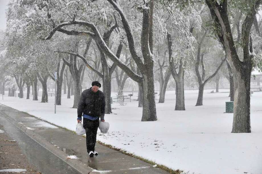 Dan Weirich walks through a scenic El Alamo Park  after an overnight storm dumped more than 2 inches of heavy, wet snow on the Texas Panhandle in Amarillo on Thursday, Oct. 27, 2011.  The National Weather Service said Amarillo received 2.5 inches of snowfall breaking the old record of 2.3 inches set in 1911 for snowfall on this date. Photo: Michael Schumacher, Associated Press / Amarillo Globe-News