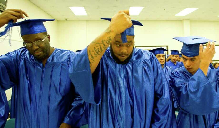 Dontreil Coats, center, and his classmates move their tassels to signify graduation during a Harris County Sheriff's Office Inmate Education Program graduation ceremony , Thursday, Oct. 27, 2011. The program, facilitated with Houston Community College, graduated fifty students, the biggest class to date. The students are trained in various vocational trades. Photo: Nick De La Torre, Houston Chronicle / © 2011  Houston Chronicle