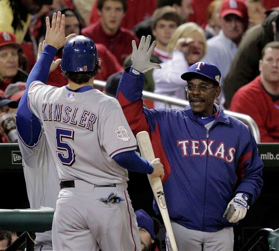 Texas Rangers manager Ron Washington congratulates Ian Kinsler (5) after Kinsler scored during the first inning of Game 6 of baseball's World Series against the St. Louis Cardinals Thursday, Oct. 27, 2011, in St. Louis. (AP Photo/Charlie Riedel) Photo: Associated Press